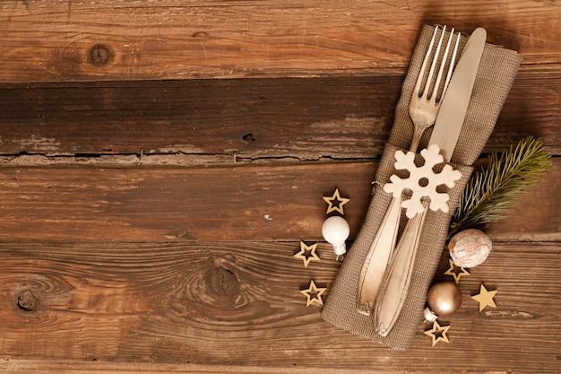 カントリースタイルのナプキンと木の表面にクリスマスの装飾がセットされたカトラリーのハイアングルショット