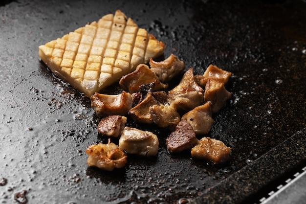 검은 쟁반에 맛있는 튀긴 고기와 감자의 높은 각도 샷