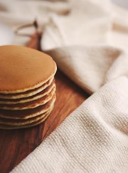Снимок вкусных блинов на деревянной тарелке под высоким углом