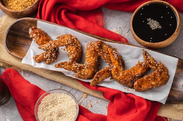 테이블에 참깨와 간장으로 맛있게 조리 된 닭 날개의 높은 각도 샷