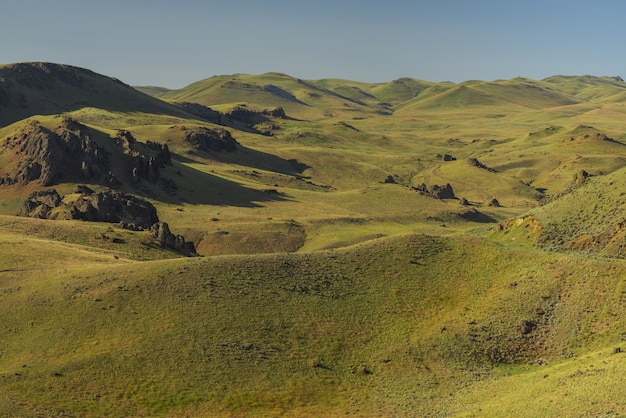 昼間の背景に青い空と空の草が茂った丘のハイアングルショット