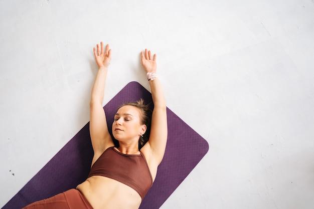 운동복을 입고 운동용 매트에 누워 운동을 하는 완벽한 운동복을 입은 젊은 여성의 하이앵글 샷. 집에서 건강한 생활 방식과 신체 활동의 개념.