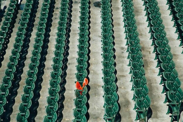 真ん中にオレンジ色の椅子が1つしかない緑色のプラスチック製の椅子の列のハイアングルショット