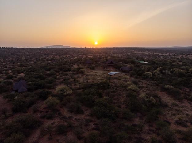 ケニアのサンブルで撮影された美しい夕日の下の木々の間の小屋のハイアングルショット