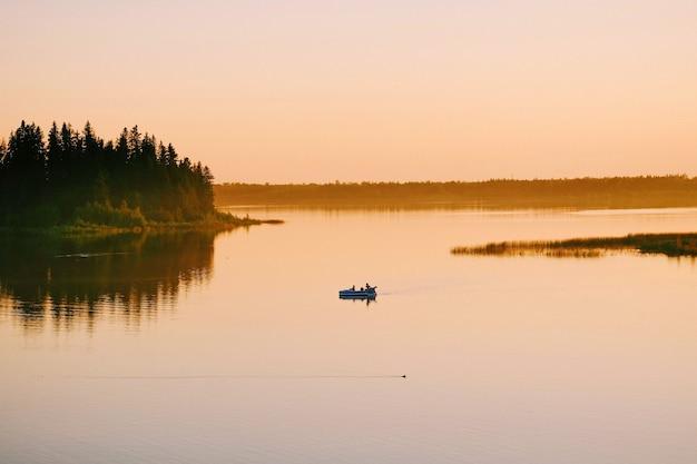 Снимок под высоким углом людей, плывущих в лодке по озеру во время заката