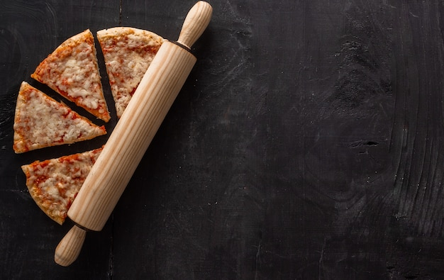 Высокий угол снимка кусочков пиццы и деревянного ролика на деревянном