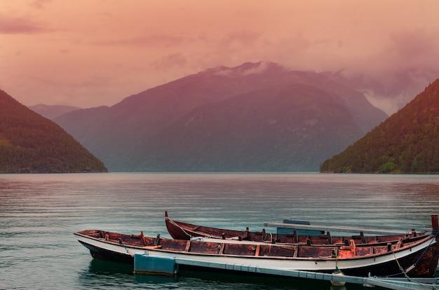 ノルウェーの日没時に高山の近くの海でさびたボートのハイアングルショット