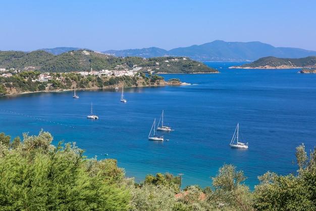 晴れた日にスキアトス島ギリシャの草が茂った丘の近くの海に帆船のハイアングルショット
