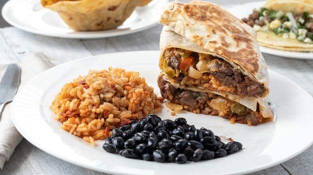 Снимок под высоким углом пряного риса, черной фасоли и мясных сэндвичей на тарелке на деревянной поверхности