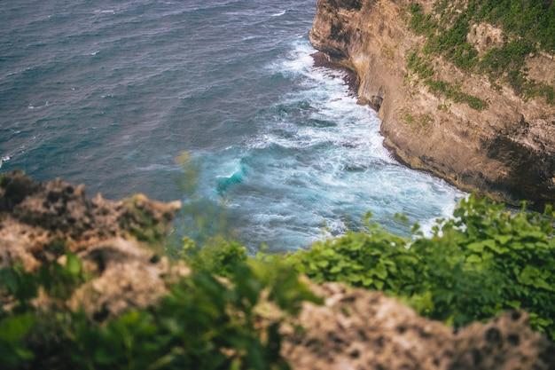 砕ける波のあるウルワツの崖のふもとのハイアングルショット