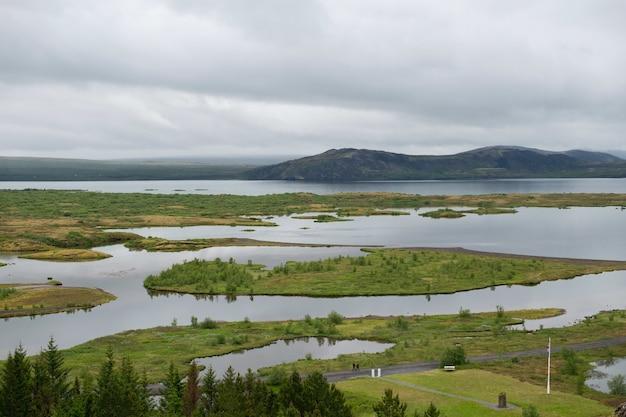 嵐の雲の下でアイスランドのシンクヴェトリルの美しい風景のハイアングルショット