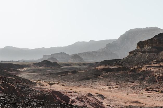 Снимок холмов в пустыне, окруженной великолепными горами, под высоким углом
