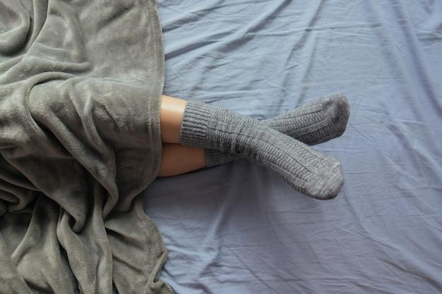 毛布の下に灰色のニット靴下を履いた女性の脚のハイアングルショット