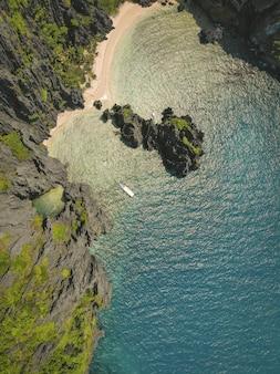 Снимок океана и пляжа под высоким углом в окружении скал, покрытых мхом