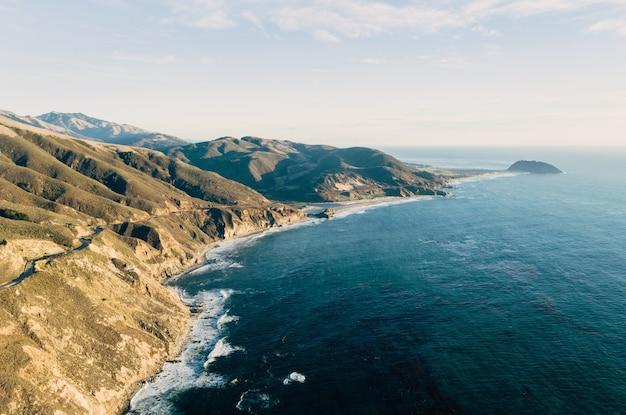 Снимок океана на скале, покрытой зеленью, под высоким углом