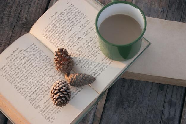 緑のコーヒーマグと松ぼっくりと2冊の本のハイアングルショット