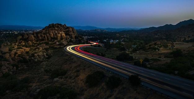 밤에 바위로 둘러싸인 고속도로에서 노란색과 빨간색 표시등의 높은 각도 샷