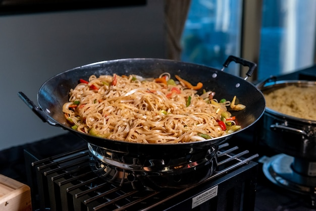 High angle shot of a pan filled with delicious noodles and vegetables in a kitchen