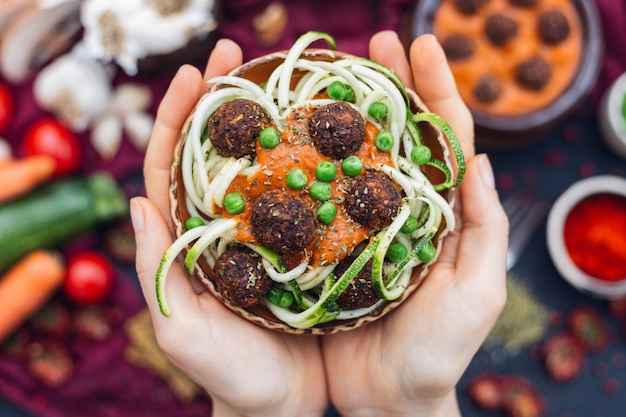 High angle shot of a person holding a bowl of delicious vegetable meatballs