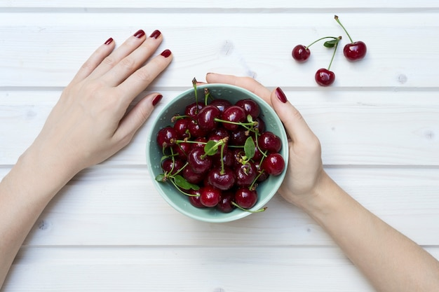 High angle shot of a person holding a green bowl of cherries on a white wooden surface