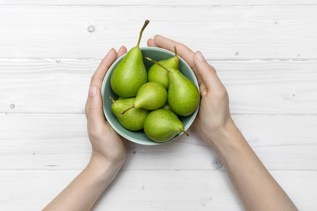 High angle shot of a person holding a green bowl of pears on a white wooden surface