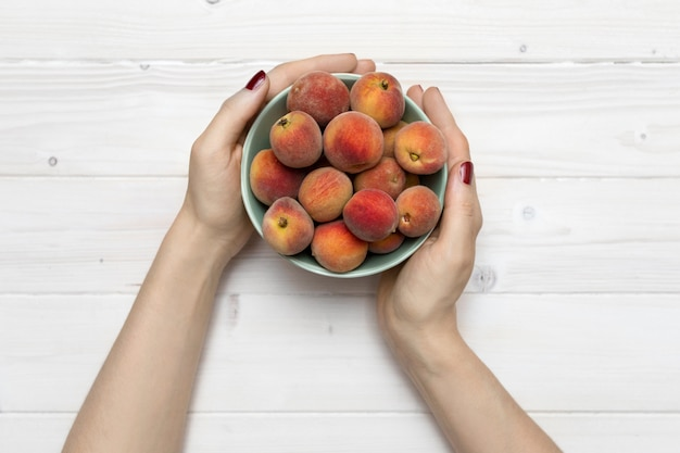 High angle shot of a person holding a green bowl with peaches on a white wooden surface