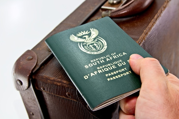 High angle shot of a person holding a passport over a leather suitcase with a white