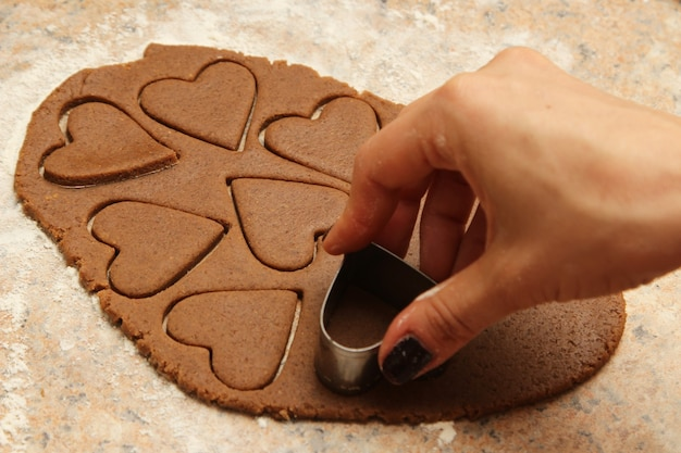 High angle shot of a person making heart-shaped cookies
