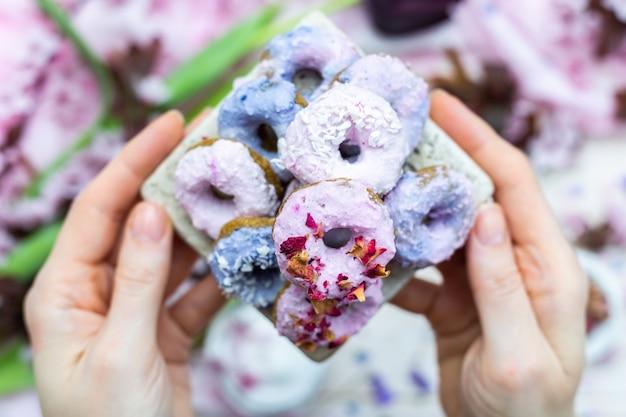 Inquadratura dall'alto delle mani di una persona che tengono alcune ciambelle vegane viola e blu su un tavolo