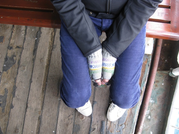 High angle shot of a person sitting on a wooden chair and holding hands together