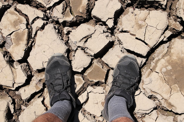 High angle shot of a person standing on the dried and cracked muddy ground