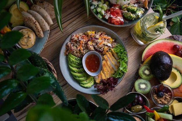 Colpo ad alto angolo di piatti di insalata e frutta fresca e verdura su una superficie di legno