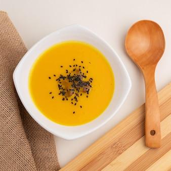 Colpo di alto angolo di zuppa di zucca con sesamo accanto a un grande cucchiaio di legno su un tavolo bianco