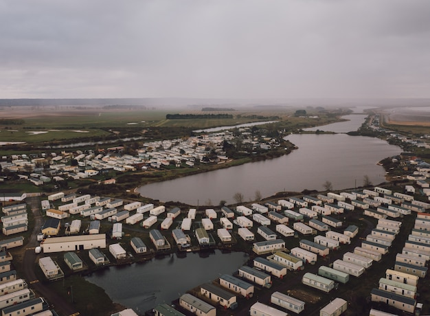 High angle shot of the rectangle houses on the fields by a beautiful foggy pond