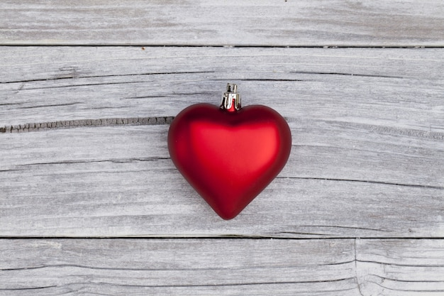 High angle shot of a red heart-shaped christmas ornament on a wooden surface