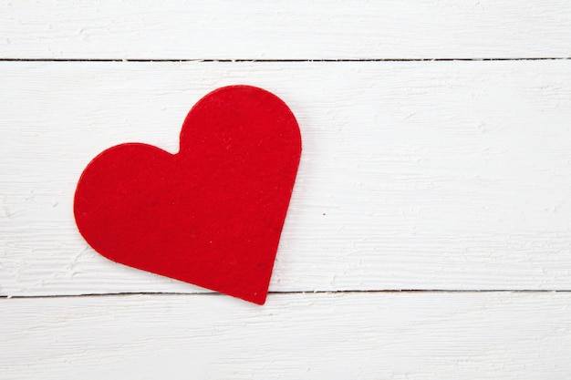 High angle shot of a red paper heart isolated on a white wooden surface