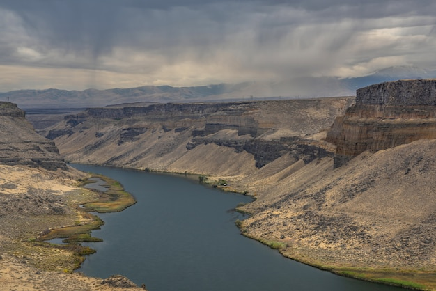 High angle shot of a river in the middle of cliffs with mountains and a cloudy sky