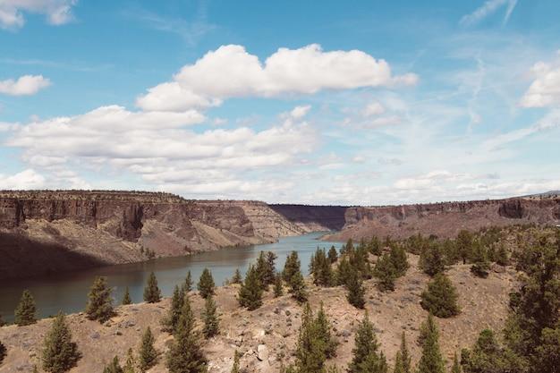 Colpo di alto angolo di un fiume circondato da colline in una zona deserta sotto il cielo nuvoloso luminoso