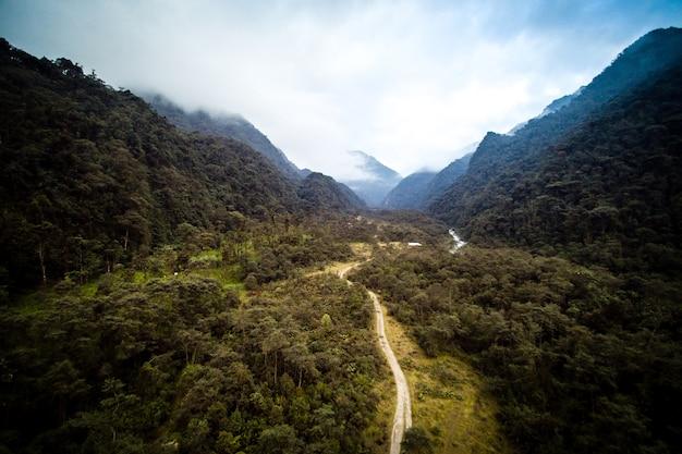 Colpo di alto angolo di una strada circondata da alberi verdi e montagne con un cielo nuvoloso