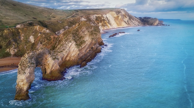 High angle shot of the rocks in the seashore of the durdle door in dorset