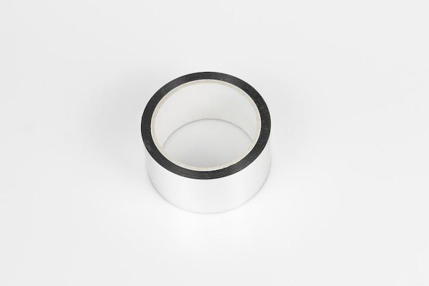 Colpo di alto angolo di un rotolo di nastro d'argento su una superficie grigia