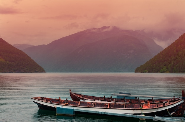 High angle shot of rusty boats on the sea near high mountains during the sunset in norway