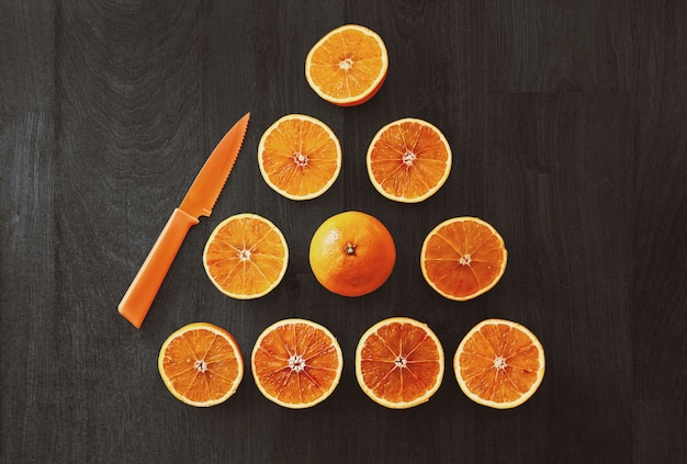 High angle shot of sliced oranges in a triangle shape beside an orange knife on a black surface