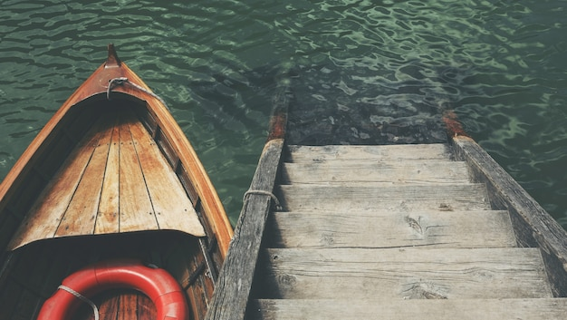 High angle shot of a small boat near the wooden stairs in the beautiful sea