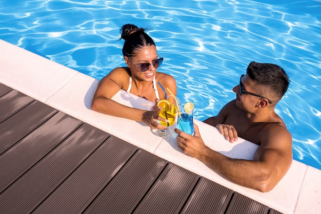 High angle shot of a smiling group of a couple holding cocktails in the swimming pool