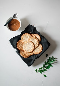 High angle shot of snacks and a bowl of caramel on a white surface