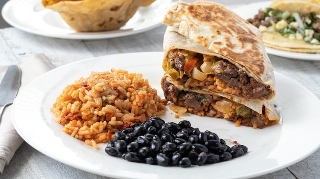 High angle shot of spiced rice, black beans, and meat sandwiches on a plate on a wooden surface