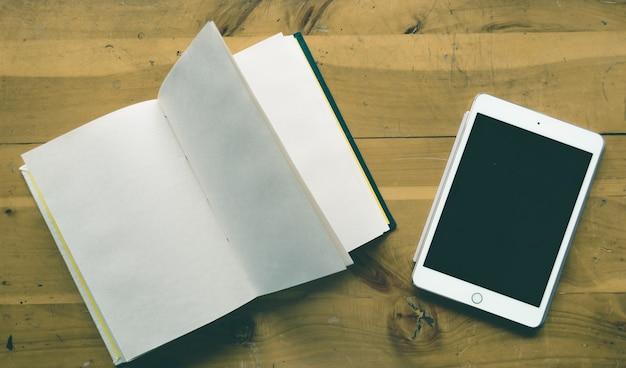 Colpo di alto angolo di una compressa e un taccuino vuoto con lo spazio della copia su una tavola di legno