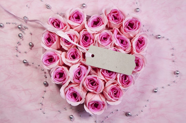 High angle shot of a tag on a beautiful heart-shaped bouquet of pink roses