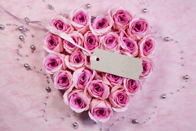 Colpo di alto angolo di un tag su un bellissimo mazzo di rose rosa a forma di cuore